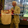 Wiscasset School Department interim Superintendent Wayne Dorr shows the Wiscasset School Board an old baseball jersey, an example of out-of-date items the department wishes to dispose of. The meeting was Dorr's final meeting as interim superintendent. (Kathy Onorato)