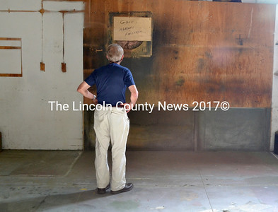 "Rudy Graf, a longtime owner of The Science Source who sold it in 2011, looks at a message recently scrawled on a piece of plywood on the wall of the company's now-former paint shop: ""Gone..... already forgotten..."" (D. Lobkowicz photo)"