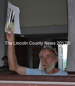 Alna resident Ralph Hilton raises his hand at a special town meeting at the Alna Meetinghouse Monday, Aug. 25. Hilton moved to amend a warrant article regarding the town's snowplowing contract. (Charlotte Boynton photo)
