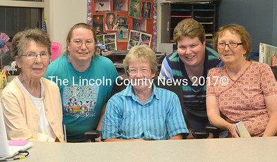 Posing behind the library's circulation desk are (from left) former librarian Theresa Burrill, current librarian Kathleen Stone, Jefferson Public Library Committee member Ann Liburt, board member and former librarian Catherine Moore, and committee memberJoan Ebbeson. (D. Lobkowicz photo)