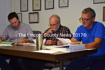 Alna Selectmen (from left) Jon Villeneuve, David Abbot and David Reingardt study proposed changes in the snowplowing contract with Hagar  Enterprises  Sept. 10. (Kathy Onorato photo)