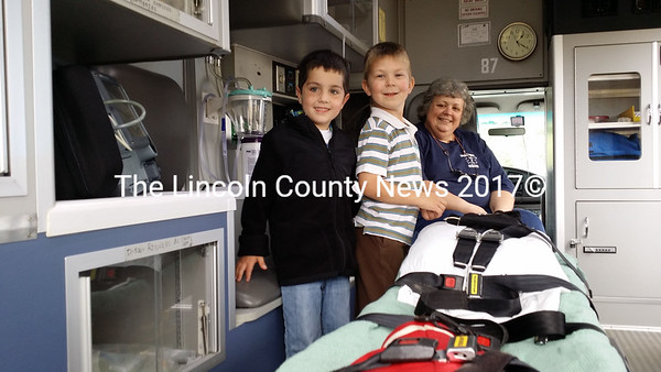 Raiden Knox (left) of Bath and Joseph Schnitzler, of Bristol, get a tour of a Wiscasset ambulance by Emergency Medical Technician Marcie Lovejoy (right). (Kathy Onorato photo)