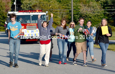 Senior class advisor Susan Jones throws up her hands and cheers and she and several seniors lead the Homecoming Parade Sept. 19. The seniors' float, a decorated fire truck, follows. (D. Lobkowicz photo)