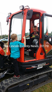 Cale Rogers (sitting), of Boothbay, and his friend Aiden Locke, of Boothbay Harbor, check out a piece of construction equipment on display during the Touch the Truck event at the Wiscasset Speedway Sept. 21. (Kathy Onorato photo)