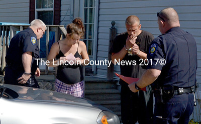 Waldoboro Police Officer Larry Hesseltine (right) arrested Devin Davis (second from right), 29, at a home on Winslows Mills Road Sept. 23. Davis was arrested on four warrants for unpaid fines, and both he and Karrie Prior, 23, were issued summons for theft from the Waldoboro Hannaford supermarket, Hesseltine said. Prior was also summoned for violation of condition of release, Hesseltine said. (D. Lobkowicz photo)
