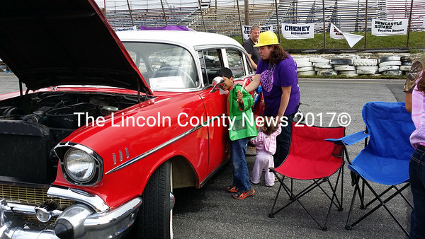 Touch the Truck organizer Aubrey Martin (right) looks over a  classic 1957 Chevy with her children Atharv (left) and Annie (center).  (Kathy Onorato photo)