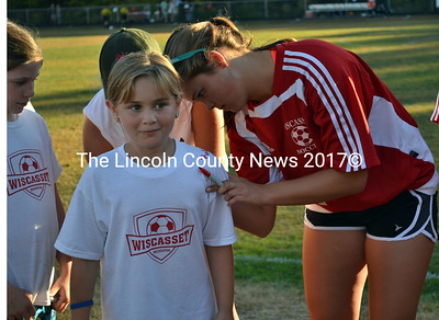 Younger ones getting their shirts signed by Wiscasset athletes has becoming a popular homecoming event. Angie Haggett gets the autograph of Miranda McIntire's during this year's homecoming.  (Kathy Onorato photo)