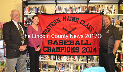 Wiscasset School officials get a first peak at Wiscasset High School's baseball championship banner Sept. 24. From left are  Lyford Beverage, interim superindent, Chelsey Hagget, school board member;  and Steve Smith, school board chairman. (Kathy Onorato photo)