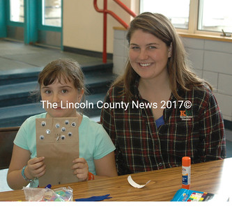 Christine Roback from Camp Kieve ran the Children's Craft table at the Nobleboro AppleFest. Emily, a third grader at Nobleboro Central School, enjoyed making paper bag monsters. (Eleanor Cade Busby photo)