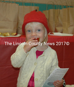 Elise Wilson, 2, thought the best part of Nobleboro AppleFest was the apples. She is wearing an apple hat made by Laurie McBurnie. (Eleanor Cade Busby photo)
