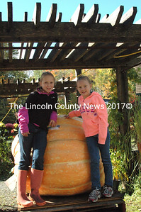 """Paris Pierpont (left) and Emaleigh Moniz paid a visit to Charlie LoPresti's Giant Pumpkin from last year's competition. Paris, who defeated her brother Justice in last year's event, did not have a giant this year. """"Mine got rotten, but I will be back and beat him next year, """" she said. (Eleanor Cade Busby photo)"""
