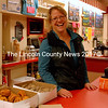 Mary Kate Reny was a popular figure at the Waltz Soda Fountain  area of Renys on Saturday morning. She was serving up free coffee, donuts and cider. The damp weather brought many to her counter  where the goodies were provided by Renys. (E. Busby photo)