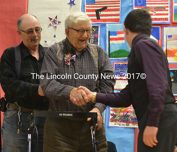 World War II veteran Fred McNally, of Waldoboro, grins as he shakes the hand of Elias Miller, the student who read McNally's brief biography at the Medomak Middle School Veterans' Day Celebration Nov. 10. McNally was later presented with a gift of an American flag. (D. Lobkowicz photo)
