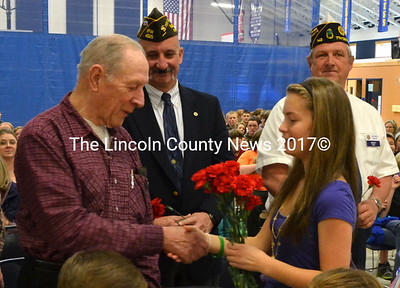 Student Paige Powell shakes a veteran's hand as she hands out carnations during Medomak Middle School's Veterans Day Celebration Nov. 10. (D. Lobkowicz photo)