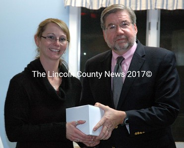 "Employee Recognition Award recipient Amy Stevens accepts a gift from Mobius Inc. President William Floyd during the agency's annual meeting in Damariscotta Monday, Nov. 10. Mobius employees nominate co-workers for the award, which recognizes recipients as ""exemplary employees and role models,"" according to Executive Director David Lawlor. (J.W. Oliver photo)"