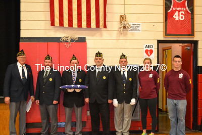 From left: American Legion Post 54 Cmdr. Bill Cossette and members Neil Page, Dale Skillin, Jim Savage, and John Kennedy, Wiscasset High School Student Council Vice President Kayla Gordon, and President Ridge Barnes prepare to raise a new American flag at the Wiscasset High School gym Friday, Nov. 14. The student council spearheaded fundraising efforts to purchase a new flag for the school. (Abigail Adams photo)