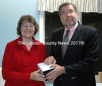 Mobius Inc. Program Manager Lucille Lothrop accepts a gift in recognition of her 20 years of employment from Mobius Inc. President William Floyd during the agency's annual meeting in Damariscotta Monday, Nov. 10. (J.W. Oliver photo)