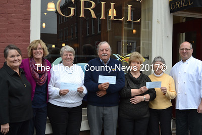 Former Anchor Inn operators Rick Hirsch and Jean Kerrigan donated the proceeds raised from a silent auction and yard sale of the restaurant's memorabilia to three area food pantries. Shown from left to right: Sharon Hobson, Kerrigan, MaryAnn Look, Ecumenical Food Pantry, Lou Cook, Waldoboro Food Pantry, and Donna Hart and Mary Alcox, New Harbor Food Pantry, and Hirsch. (Michelle Switzer photo)