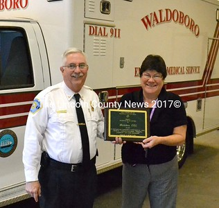 Standing in front of Waldoboro's just-arrived new ambulance, Director Richard Lash and Town Manager Linda-Jean Briggs hold up Waldoboro EMS's regional EMS Service of the Year 2014 award. (D. Lobkowicz photo)