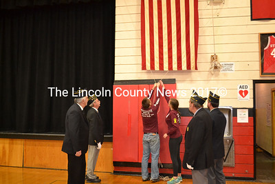 Wiscasset High School Student Council Vice President Kayla Gordon and President Ridge Barnes lower Wiscasset High School's old American flag as American Legion Post 54 members look on at a special flag assembly Friday, Nov. 14. (Abigail Adams photo)