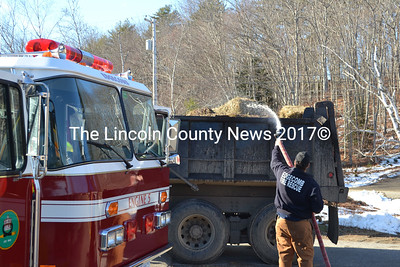 Edgecomb firefighter Kevin Brewer soaks hay inside an N.A. Reny Construction Inc. dump truck in the Skip Cahill Tire parking lot in Edgecomb Tuesday, Dec. 2. Holes in the truck's body exposed the exhaust to the hay, according to Edgecomb firefighter Wally Staples. (Michelle Switzer photo)