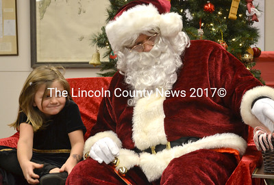 Kaylee Sidelinger, 6, smiles bashfully as Santa Claus selects a candy cane for her. (D. Lobkowicz photo)