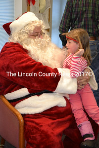 Dezirae Colby tells Santa Claus she would like a baby doll for Christmas before having breakfast with her dad Saturday morning at the Wiscasset Community Center's annual Breakfast with Santa event. (Charlotte Boynton photo)