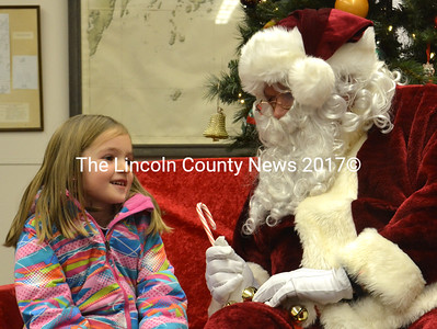 Santa Claus offers a candy cane to Kate Prior, 5, as he listens during their visit Dec. 14. (D. Lobkowicz photo)