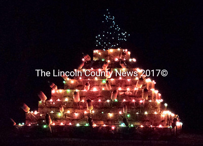 A traditional Christmas tree tops a lobster trap tree complete with buoy ornaments on Kaler's Corner Road in Waldoboro. (D. Lobkowicz photo)