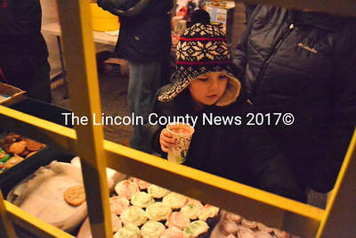 Holding a hot drink, Carson Crabtree, 6, of Waldoboro selects a treat during Waldoboro's Christmas celebration Dec. 21. (D. Lobkowicz photo)