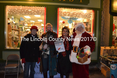 "Toni Crouch, Marva Nesbit, and Cindy Wade, (left to right) of the Damariscotta Region Chamber of Commerce stand with Santa Claus and dog Nico to promote a new program called Beat the Winter Blahs, during the Twin Villages Wrap it Up Party Dec. 18. ""For $20 a card, members can save over $350 total,"" Nesbit said. (Michelle Switzer photo)"