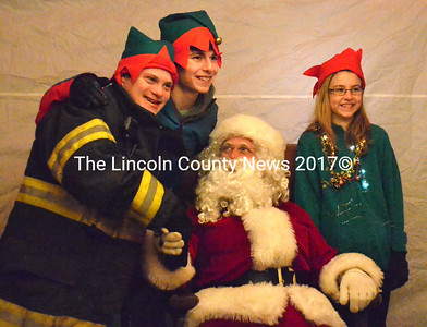 Santa Claus poses with local elves (from left) Myles Frederick, Aaron Smeltzer, and Quinn Overlock during his visit to Waldoboro. (D. Lobkowicz photo)