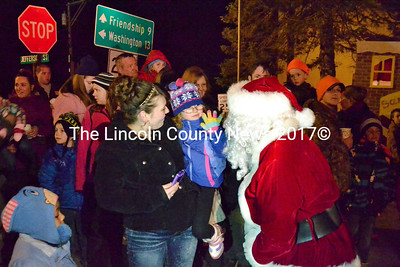 Santa Claus, fresh off Waldoboro Fire Department's ladder truck, visits with Isabella Tolman, 5, of Waldoboro, and Kristina Hall. A sizeable crowd gathered on the corner of Jefferson and Main streets in the village in anticipation of the jolly old elf's arrival.(D. Lobkowicz photo)