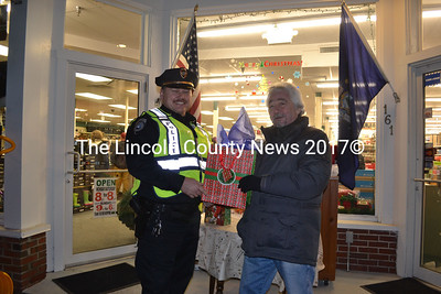 Damariscotta Police Chief Ron Young and local volunteer Greg Latimer stand at the Reny's Underground wrapping station during the eighth annual Wrap it Up Party, Dec. 18.