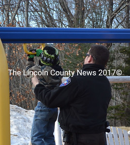 Lincoln County Sheriff's Deputy Jared Mitkus helps an Edgecomb Eddy student reach the Magyver swing during recess Dec. 19. (Michelle Switzer photo)