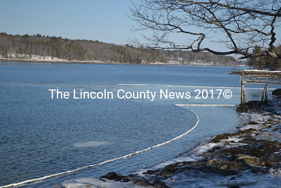 Containment booms contain diesel fuel spilled into the Damariscotta River from a sunken barge near Mook Sea Farms in Walpole, Feb. 7.