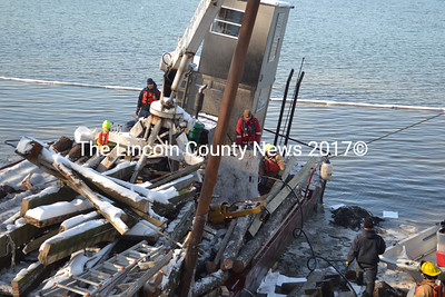 Members of the Lincoln County Hazardous Materials Response team tend to a sunken barge near the wharf owned Mook Sea Frms in Walpole. Owned by Round Pond Marine, the barge sank sometime during the overnight hours Feb. 6-7. (Sherwood Olin photo)