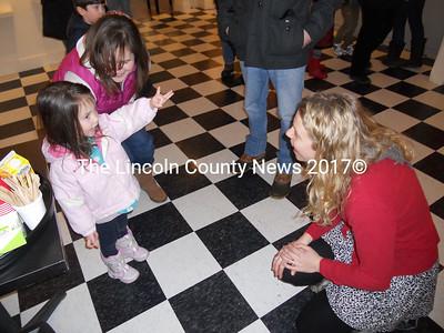 Waldoboro Middle School art instructor Brooke Holland (right) talks art with future artist, Kirstan Creamer, 3, with her mom, Jana Creamer, all of Waldoboro. (K. Fletcher photo)