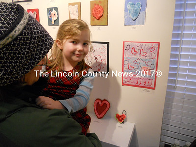 In her mother Kathy Osborne's arms, kindergarten student Anya Osborne shows her artwork (right) that graces the Tidewater Gallery space in Waldoboro. (K. Fletcher photo)