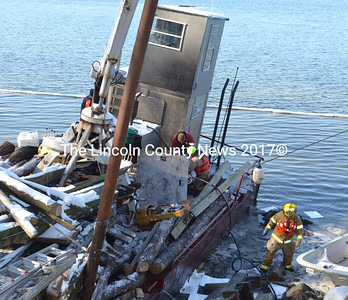 Members of the Lincoln County Hazardous Materials Response team tend to a barge that sank near the wharf owned Mook Sea Farms in Walpole sometime during the sometime during the overnight hours Feb. 6-7. (Sherwood Olin photo)