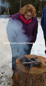 Wiscasset Town Manager Laurie Smith checks out a Swedish bonfire at Winterfest. (Kathy Onorato photo)