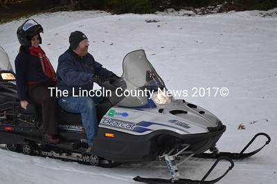 Amy Constantine (left) enjoys her first snowmobile ride offered by Tim Soule of the Wiscasset Sno-Goers.  (Kathy Onorato photo)