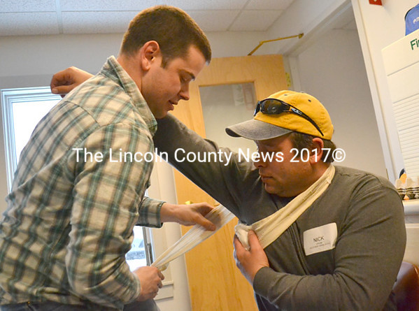 Lincoln County Sheriff's Deputy Jared Mitkus practices applying a dressing to a would-be armpit wound on Boothbay Harbor Police Reserve Officer Nick Upham. (D. Lobkowicz photo)