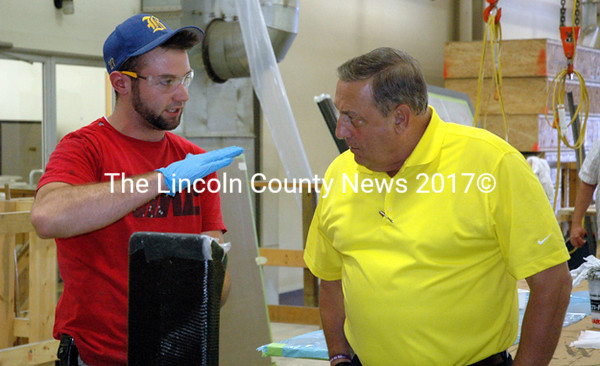 Maine Gov. Paul LePage talks with composite technician Scott Alley during a tour of the Hodgdon Yachts Inc. facility in East Boothbay Wednesday, 
