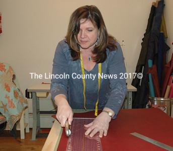 Tori Anna Dyke cuts leather for a new purse at Tori Anna Designs in Damariscotta, April 29. (J.W. Oliver photo)