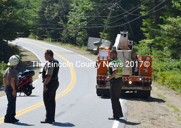 Lt. Rand Maker (center) and Deputy Kevin Dennison (right) of the Lincoln County Sheriff's Office consult with a firefighter at the scene of a single-vehicle accident on Route 129 in South Bristol Tuesday, Aug. 26. The box truck in the background hit a utility pole, causing a power outage in the area. (Kathy Onorato photo)