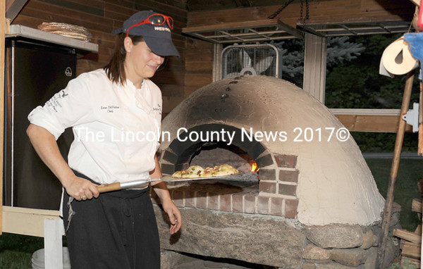 Lara DePietro removes a pizza from the woodburning oven at Squire Tarbox Inn and Restaurant on Westport Island.