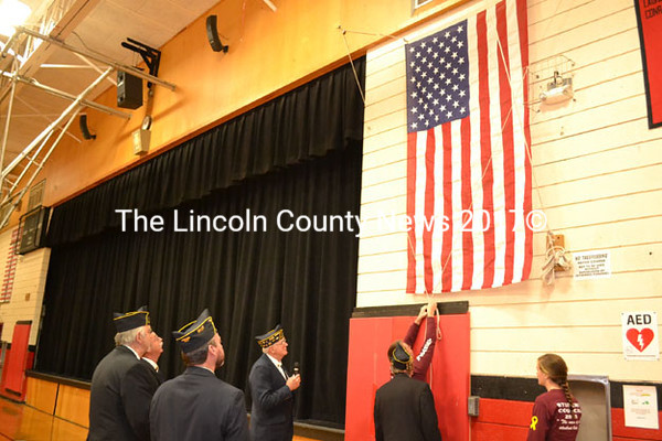 Wiscasset High School Student Council President Ridge Barnes secures Wiscasset High School's new American flag while Vice President Kayla Gordon and American Legion Post 54 members look on Friday, Nov. 14. (Abigail Adams photo)