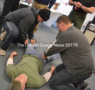 Under a time limit, Waldoboro police officers practice basic life-saving treatments. Sgt. Jamie Wilson (right) applies a tourniquet to the leg of Officer John Lash, as Officer Thomas Bartunek checks Lash for other wounds. (D. Lobkowicz photo)