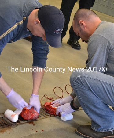 Lincoln County Sheriff's Detective Scott Hayden (right) and Waldoboro Police Department Reserve Officer Andrew Santheson pack gauze into simulated wounds in pieces of meat as part of tactical casualty care training. (D. Lobkowicz photo)